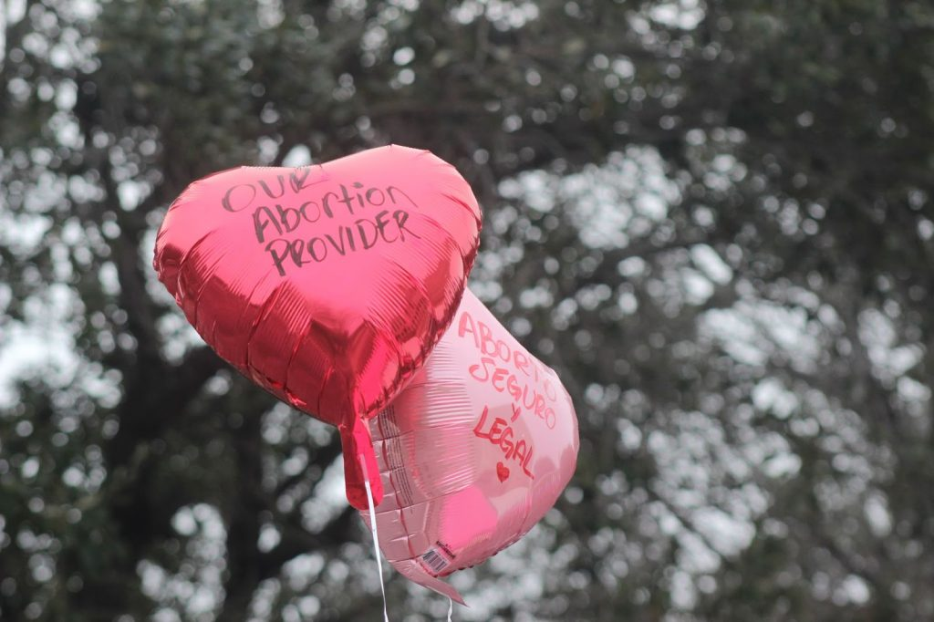 """Balloons with """"Love Our Abortion Provider"""" and """"Aborto Seguro y Legal (Safe and Legal Abortion)"""" written on them at the February 2019 We're Still Here March at Whole Woman's Health Clinic in McAllen, Texas. 📷 by Freddy Jimenez."""